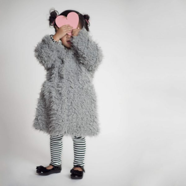 Little girl in coat holds up a pink paper heart