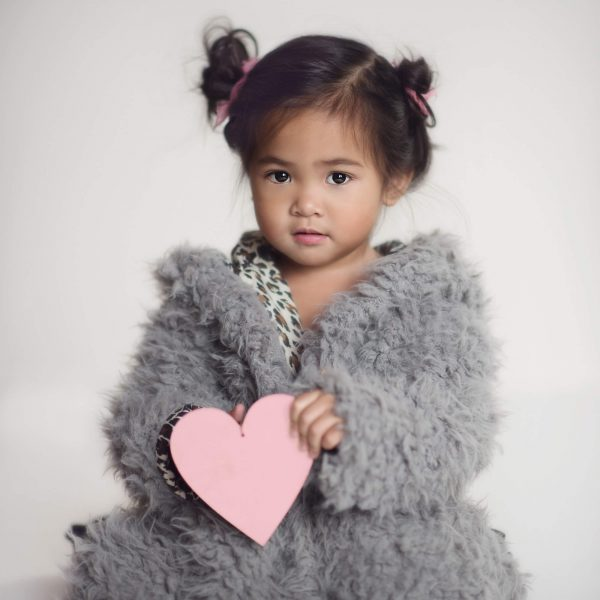 Infant Girl Holding a Paper Heart Wearing a Furry Coat